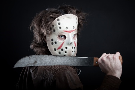 horrible maniac in mask with machete posing over dark background
