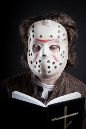 Maniac reading the Bible over dark background Stock Photo - 12163788