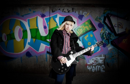 Pretty blonde girl with black guitar posing over wall with graffiti photo