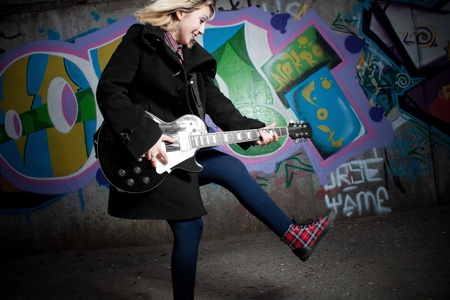 Fury rocker girl playing over wall with graffiti