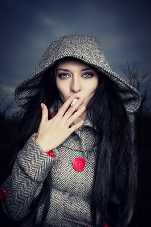 Smoking pretty dark-haired girl standing over cloudy octrober sky