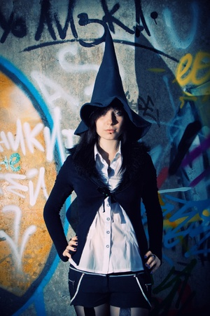 witchery: Pretty witch posing over wall with graffiti