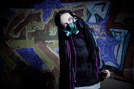 Pretty cyber gothic girl with gas mask posing over graffiti photo