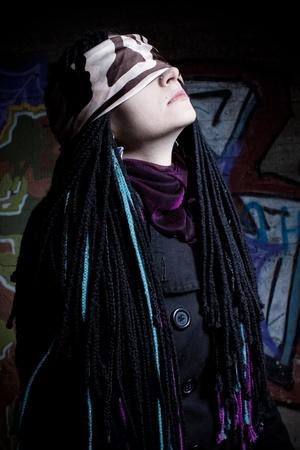 blindly: Chica linda con rastas y de la banda haci�ndose pasar por sobre el muro Foto de archivo