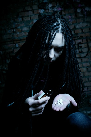 opiate: sad girl posing in the dark room with pills Stock Photo