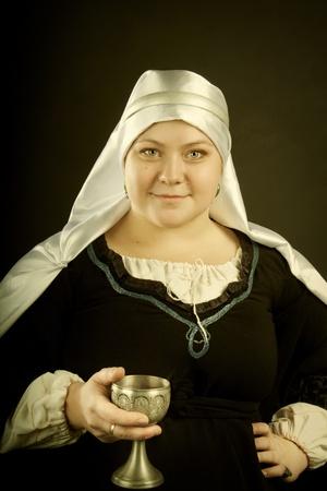 xv century: Medieval european woman with gablet posing over dark background. XV century.