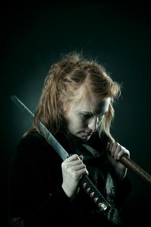 katana: Mooie roodharige meisje met katana staan in de duisternis
