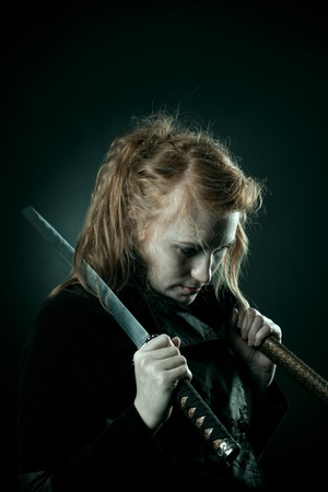 katana sword: Pretty redhead girl with katana standing in the darkness