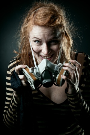 Pretty redhead girl with gas mask speaking over dark background photo