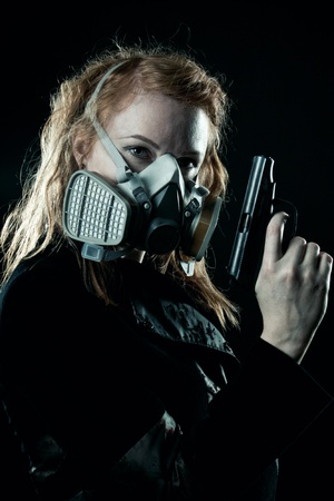 Redhead serious woman with pistol and gas mask posing over dark background photo