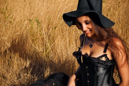 wicked woman: Pretty funny witch sitting in the field