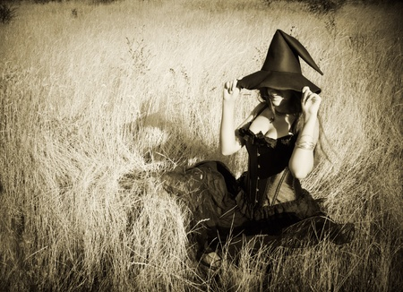 Pretty funny witch sitting in the field