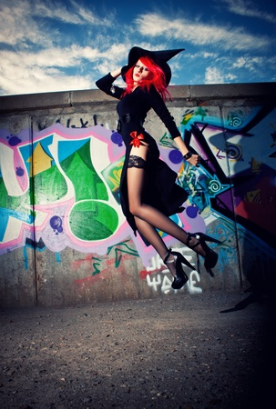 witchery: Pretty sexy redhead witch jumping over wall with graffiti