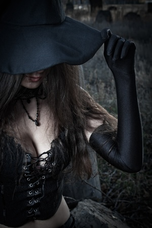 Pretty sexy witch in corset posing over field