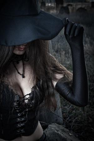 strega: Bella sexy strega in corsetto posa sopra il campo