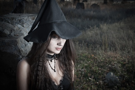 Pretty sexy witch in corset posing over field Stock Photo - 12639766