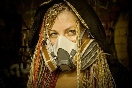 The world after nuclear war  Shot of pretty girl with dreadlocks in gas mask  photo