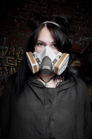 Pretty dark-haired girl in gas-mask posing over wall photo