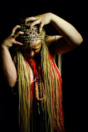 African young woman with dreadlocks posing over darkness photo