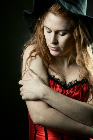 red corset: redhead pretty witch in red corset posing over dark background