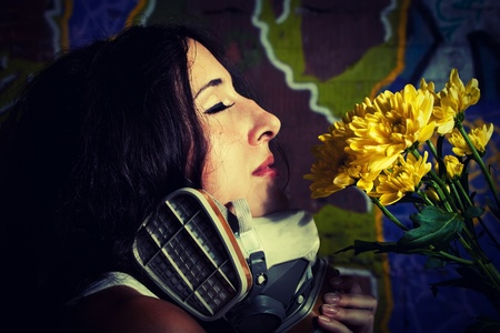 Pretty girl with gas mask and flowers posing over wall with graffiti photo