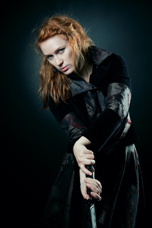 female assassin: Pretty redhead girl fencing over dark background