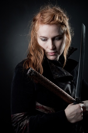 bloodthirsty: Pretty redhead girl with katana standing in the darkness