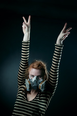 Redhead girl in respirator showing victory sign photo