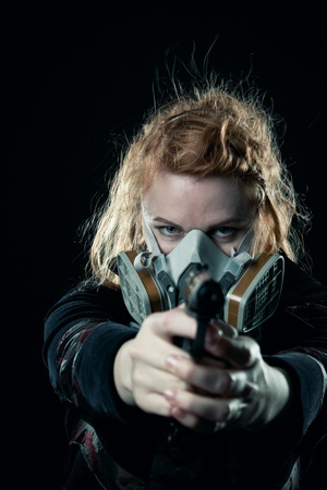 Redhead serious woman with pistol and gas mask posing over dark background