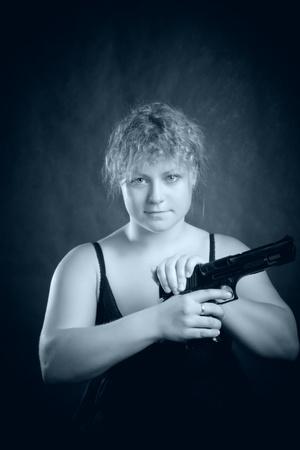 pretty blondie with gun posing over dark background Stock Photo - 12861966
