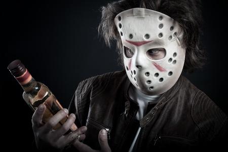 debauch: Horrible maniac in mask holding bottle posing over dark background Stock Photo