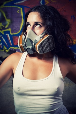 Pretty young girl in respirator posing over wall with graffiti photo