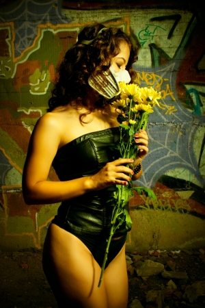 Pretty sexy girl in respirator posing with flowers over wall  photo