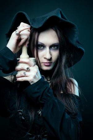 pretty witch with mortar and  pestle over dark background Stock Photo - 13100874