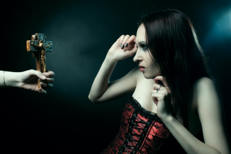 Pretty scared vampire posing over dark background photo