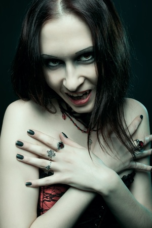 Pretty gothic girl posing over dark background photo
