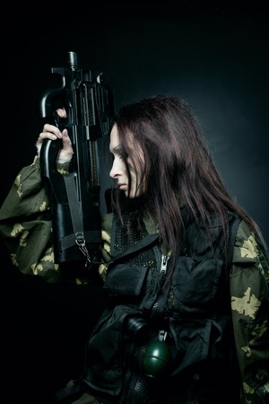 Military girl with fn p90 posing over dark background photo