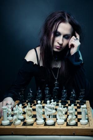 Pretty gothic girl playing chess over dark background Stock Photo - 13228098