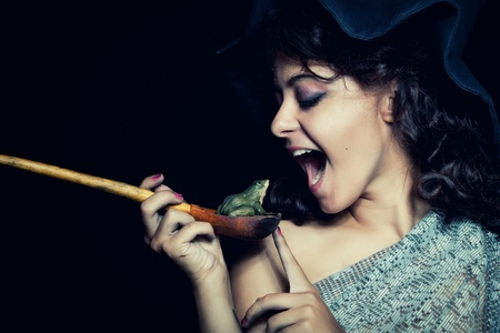 Pretty witch in hat eating frog over dark background photo
