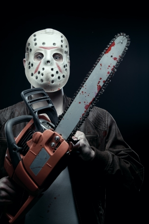 Maniac in mask holding bloody chainsaw photo