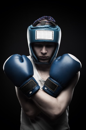 Young man in blue boxing glove posing over dark background
