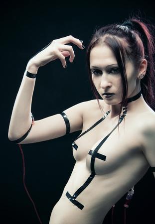 Pretty futuristic cyber girl posing over dark background photo