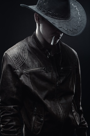cowboy with cigarette posing over dark background