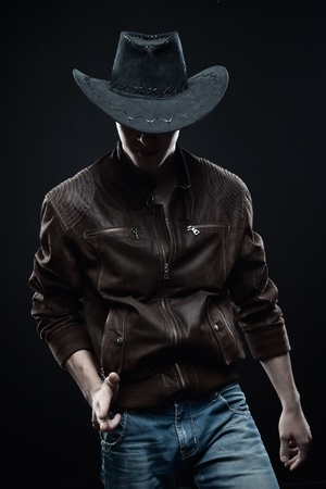 cowboy in hat posing over dark background Stock Photo - 13538369