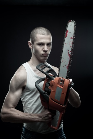 Horrible maniac holding bloody chainsaw over dark background photo