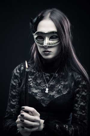 Pretty gothic girl in mask holding candle over dark background photo