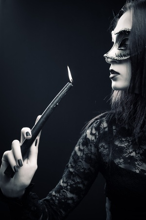 gothic: Pretty gothic girl in mask holding candle over dark background
