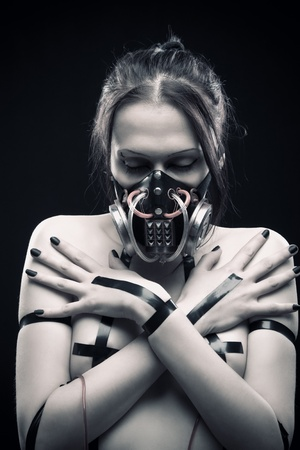 Pretty cyber gothic girl in respirator posing over dark background photo