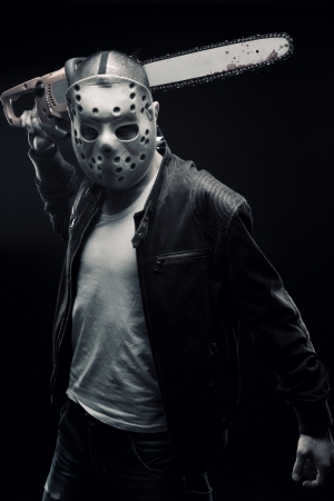 Man in mask with chainsaw posing over dark background photo
