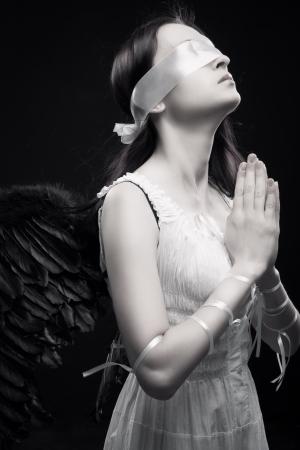 gothique: Jolie fille avec des ailes artificielles prier sur fond sombre